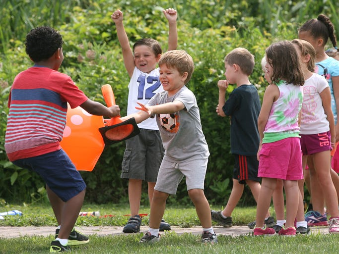 """Children run a torch relay game as the Township of Morris Parks & Recreation Department host their annual Junior Olympics. Chase Bright, hands off the """"torch"""" to another child as Tyler Bermudez cheers, July 10 2014. Morris NJ. photo by Kathy Johnson MOR 0711 Junior Olympics"""