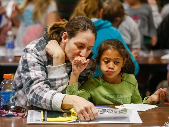 Kimberly Davidson kisses her daughter Halei Davidson's, 5, hand while looking at a worksheet with the alphabet on it during parent night at York Elementary School on Thursday, Feb. 1, 2018.