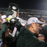 Michigan State coach Mark Dantonio and his wife, Becky, embrace after his team received the Big Ten East Division Championship trophy after beating Penn State, 55-16, on Saturday in East Lansing.
