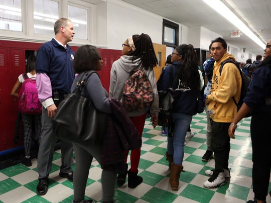 Principal Edward DeChent talks to students in the hall