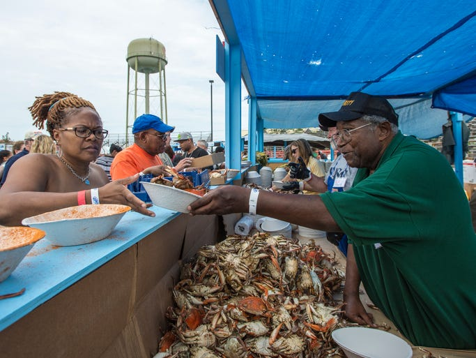 Longtime volunteer Cliff Horsey serves up crabs to ECI employee Pamela Trower of Princess Anne during the 38th annual J. Millard Tawes Crab & Clam Bake in Crisfield.
