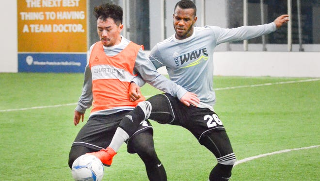 Milwaukee Wave players Mathew Yang (left) and Ian Bennett vie for the ball during practice Monday at the Midwest Orthopedic Sports Complex in Brookfield. Bennett leads the MASL with 15 goals through seven games for the undefeated Wave.