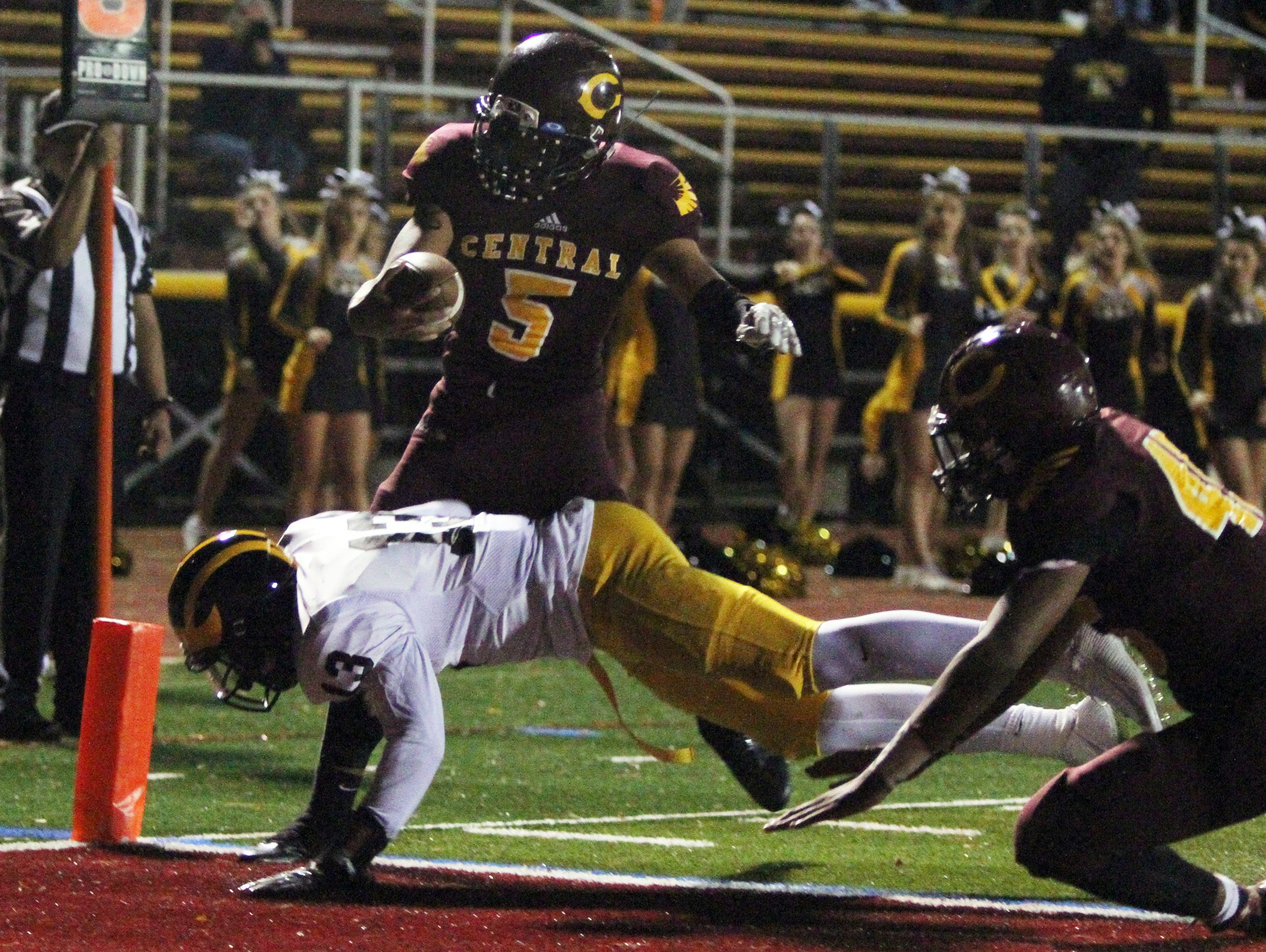 St. John Vianney at Central Regional High School football game held in Berkeley Twp. on Friday September 25 , 2015. Here Central Regional's # 5 quarterback Michael Miserendino gets around a diving tackle attempt from St. Joihn Vianney's # 13 (lower) Anthony Brown for a touchdown.