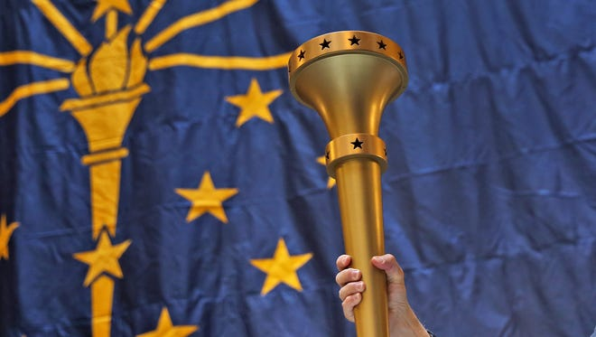 Gove. Mike Pence holds up the Indiana Bicentennial Torch during the Statehood Day Celebration at the Statehouse, Friday, Dec. 11, 2015. This begins the celebration of Indiana's 199th birthday.