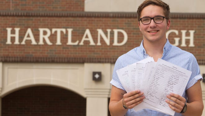 Hartland High School junior Emilio Horvath holds eight pages of petition signatures with 165 signatures in front of the high school Thursday, Sept. 14, 2017. The petition requests a moment of silence in remembrance of 9/11, a practice that had been followed in the past, but didn't happen this year.