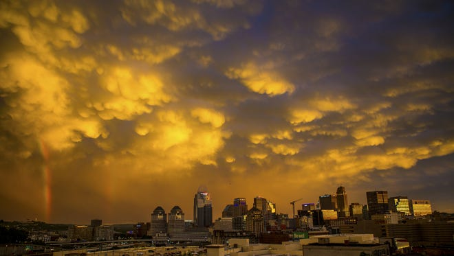 """A double rainbow appears after a thunderstorm in Cincinnati Wednesday, June 15, 2016.As I was coming home from an assignment, I watched this scene unfold. I ran up to the roof of my building and stood on the ladder in awe. The skyline looked like a painting. One of my favorite parts of this photo is the green """"Be Well"""" billboard from Mercy Health."""