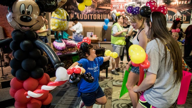Fallon West, 5, talks with Maddie Cartwright, 17, and Emeline Freeman, 17, during a celebration party after her return from Disney World.