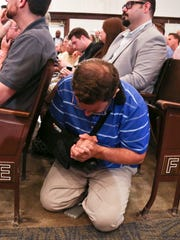 One man prays on his knees during Kentucky Gov. Matt Bevin's speech about a way to help curb violence Thursday morning at Western Middle School.