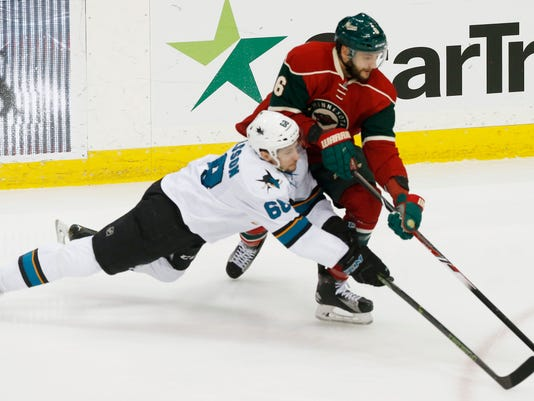 San Jose Sharks' Melker Karlsson, left, of Sweden, falls as he battles for the puck with Minnesota Wild's Marco Scandella in the first period of an NHL hockey game Tuesday, April 5, 2016, in St. Paul, Minn. (AP Photo/Jim Mone)