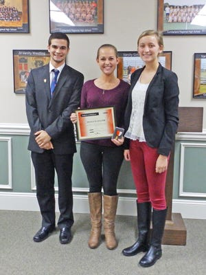 Shaelyn Halter (center), a senior at Cumberland Regional High School and the Colt Citizen of the Month for November, is congratulated by Board of Education student representatives Robert Erianne and Carly Malestein.
