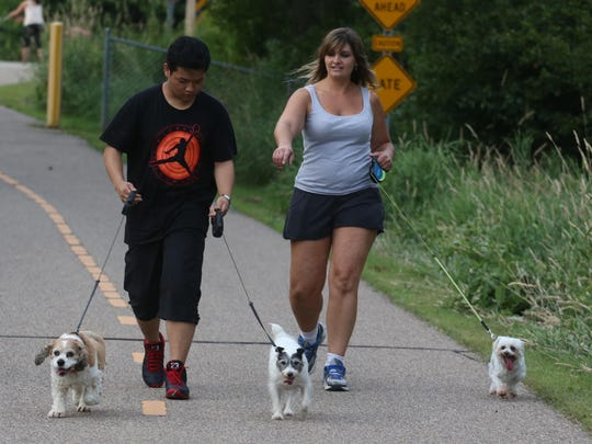 Kari Schaefer of Marshfield directs Chinese immersion student Wan Ruixuan on Friday, July 24, as they walk Schaefer's dogs in Marshfield.