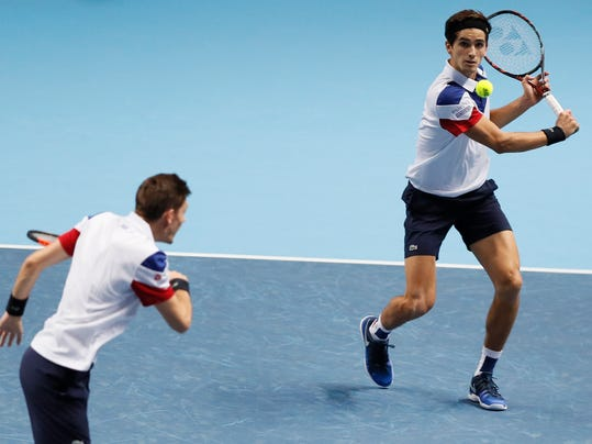 Pierre-Hugues Herbert of France, left, and Nicolas Mahut of France play a return Jean-Julien Rojer of the Netherlands and Horia Tecau of Romania during their doubles tennis match at the ATP World Finals at the O2 Arena in London, Sunday, Nov. 12, 2017. (AP Photo/Kirsty Wigglesworth)