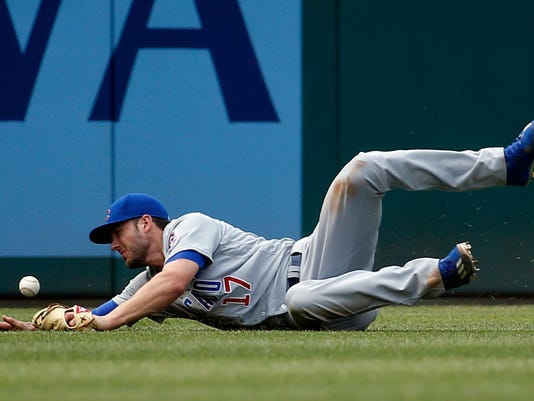 Chicago Cubs left fielder Kris Bryant can't catch a ball hit by Washington Nationals' Jayson Werth, but Bryant threw out Werth at second base, during the sixth inning of a baseball game at Nationals Park, Wednesday, June 15, 2016, in Washington. (AP Photo/Alex Brandon)