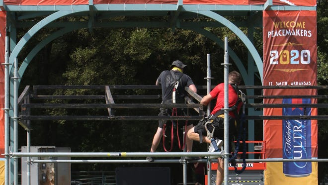 Little Rock City Staging's Mike Curtis, left, and Jeremy Josephson build the front of house, Thursday, July 23, 2020, for the weekend Peacemaker music festival at Fort Smith's Riverfront Park.