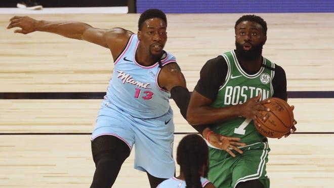 Boston Celtics guard Jaylen Brown (7) drives against Miami Heat forward Bam Adebayo (13 ) during the first half of Tuesday night's game in Lake Buena Vista, Fla.