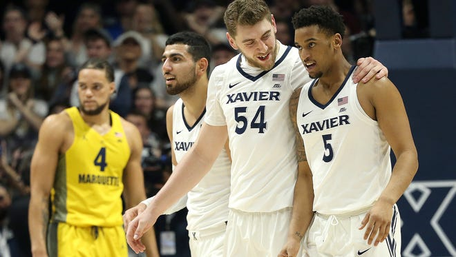 Xavier Musketeers forward Sean O'Mara (54), center, congratulates Xavier Musketeers guard Trevon Bluiett (5), far right, after he scored his 2,000th career point in the second half during the NCAA basketball game between the Marquette Golden Eagles and the Xavier Musketeers,  Wednesday, Jan. 24, 2018, at Cintas Center in Cincinnati. Xavier won 89-70.