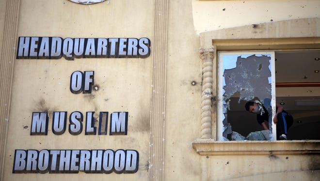 An Egyptian protester ransacks the Muslim Brotherhood headquarters in July.