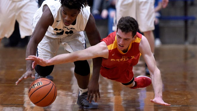 Tamaje' Blackwell of Reitz dives for a loose ball along with Jared Abney of Mater Dei during the first quarter of the game at Reitz in Evansville Friday.
