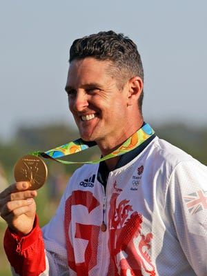 Justin Rose of Great Britain, holds up the gold medal after during the final round of the men's golf event at the 2016 Summer Olympics in Rio de Janeiro, Brazil, Sunday, Aug. 14, 2016.