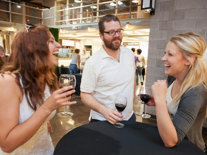 Friends laugh over wine during the Downtown Phoenix