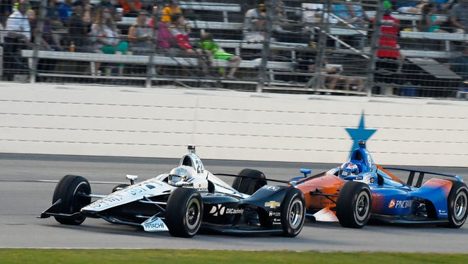 Simon Pagenaud (22) of France and Scott Dixon (9) of New Zealand battle for position during an IndyCar auto race, Saturday, June 9, 2018, in Fort Worth, Texas. Dixon won the race. (AP Photo/Larry Papke)
