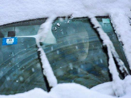 A driver looks through a snow-covered windshield during