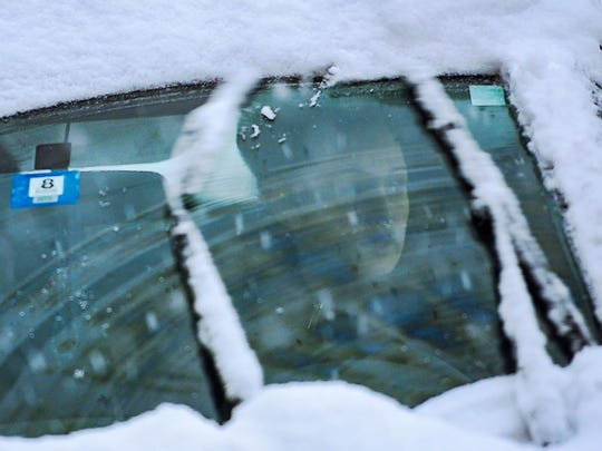 A driver looks through a snow-covered windshield during the evening commute in Burlington on Friday, December 22, 2017.