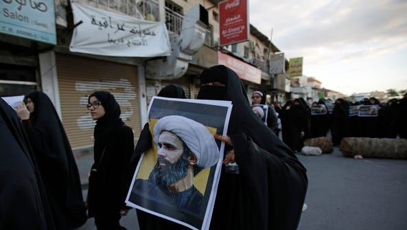 A Bahraini protester holds a picture of Saudi Shiite