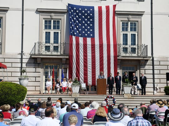 Names of those killed during various wars are read during the Memorial Day service at the War Memorial in Grosse Pointe Farms, Mich. on May 28, 2018.