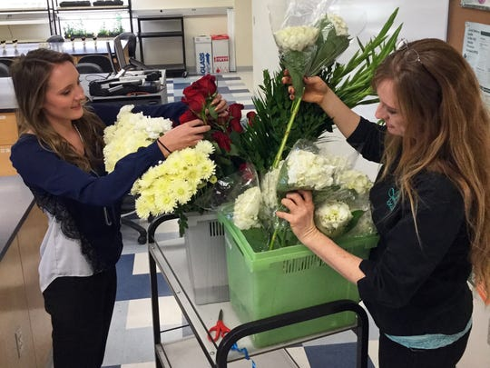 New Mexico State University Floriculture Program student Belle Morrow, left, and program coordinator and certified floral designer Sabine Green sort through various flowers.