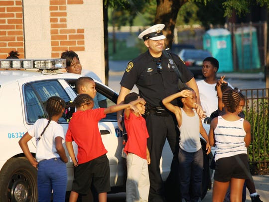 A few hours after the shooting, a Cincinnati police officer poses for a picture with children from the Boys and Girls Club in Avondale.