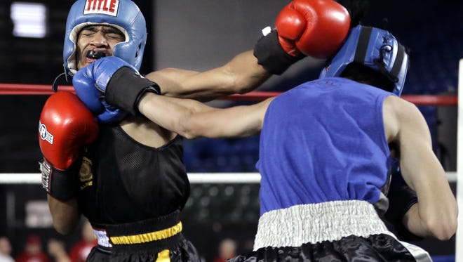 Alden Smith, right, connects to the face of Isiah Fierro in their 120-pound bout Saturday at the El Paso Regional Golden Gloves at the El Paso County Coliseum . Smith scored a TKO win over Fierro. The bouts continue Sunday beginning at 2:30 pm.