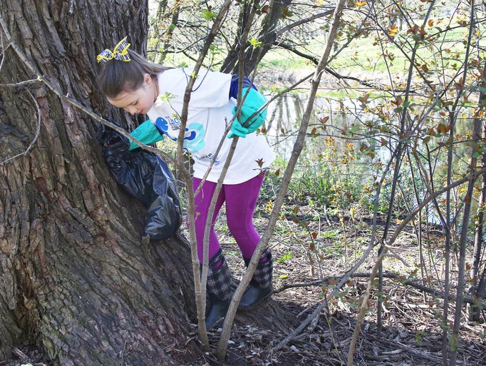 Katie Watry, 7, makes her way through brush along the