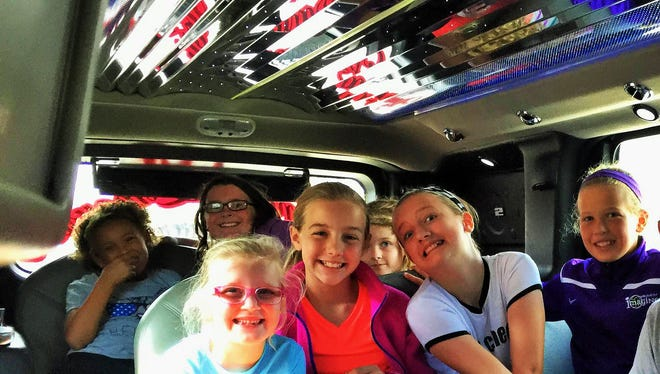 With ceiling lights pulsating to the music, top fundraising students from a North Liberty elementary school were rewarded with a limousine ride to lunch.