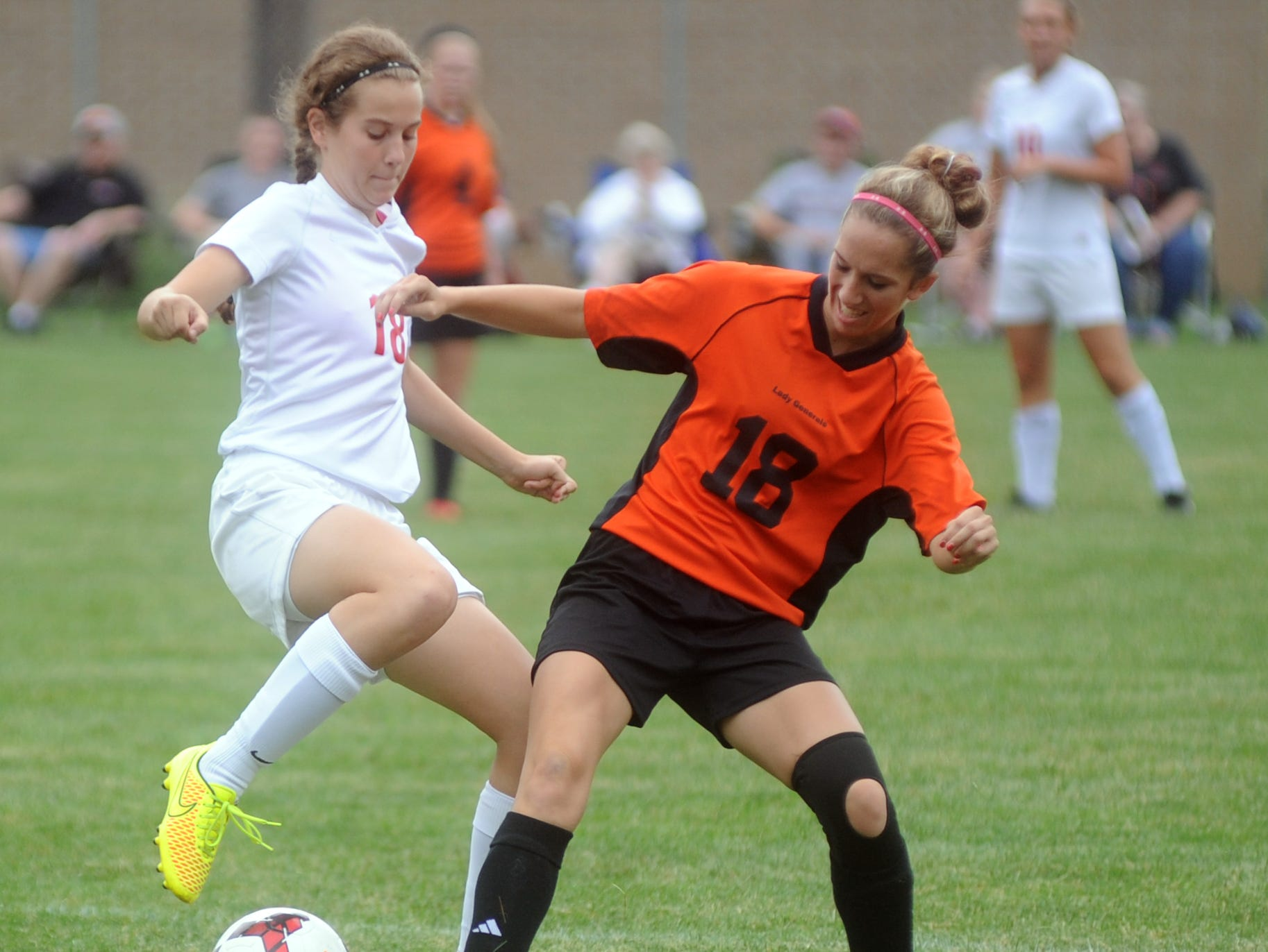Coshocton's Kenzie Mizer and Ridgewood's Marissa Whitt fight for the ball during Thursday's game.