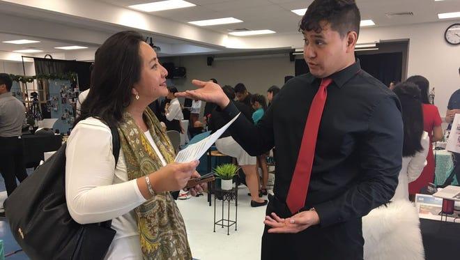 Visual communication student Sean Davis talks to Michelle Quichocho, vice president of ASC Trust, at the Guam Community College Reverse Job Fair on April 11, 2018.