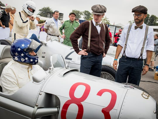 Classic racing cars line up ahead of a race during