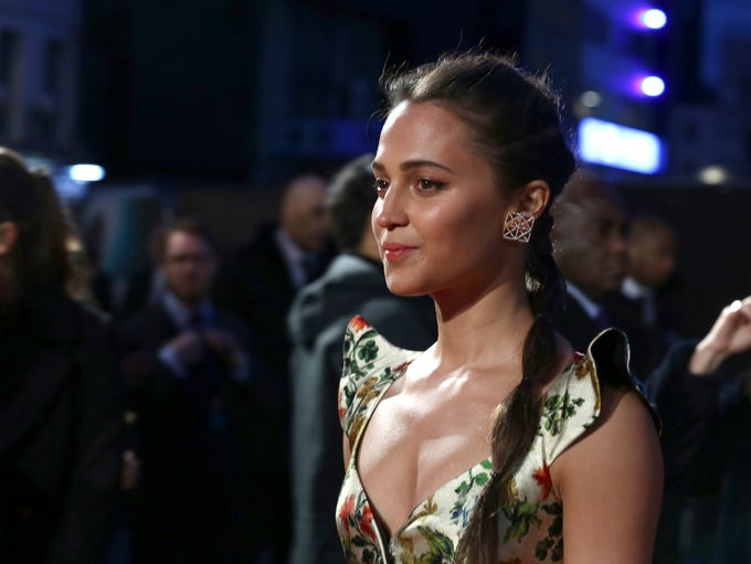 Actress Alicia Vikander poses for photographers upon