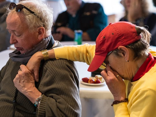 Sam Mills and Roxanne Frith become emotional as they hear about the condition of their long-time friend Barbara Morris at a fundraiser in Lansing's Old Town Sunday, Oct. 23, 2016.