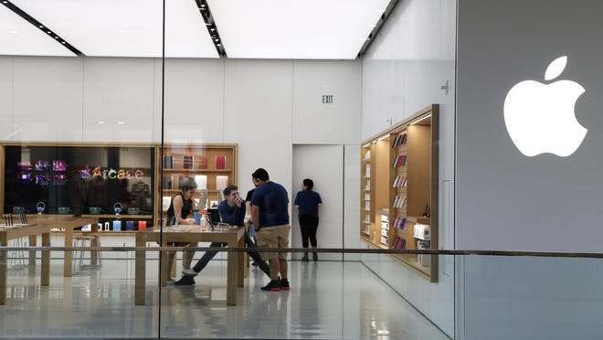 FILE - In this March 14 2020 file photo, Apple employees work inside a closed Apple store in Miami. Apple is temporarily closing 11 stores in Arizona, Florida, North Carolina and South Carolina just few weeks after reopening them in hopes that consumers would be able to shop in them without raising the risk of infecting them or company workers with the novel coronavirus that caused COVID-19.