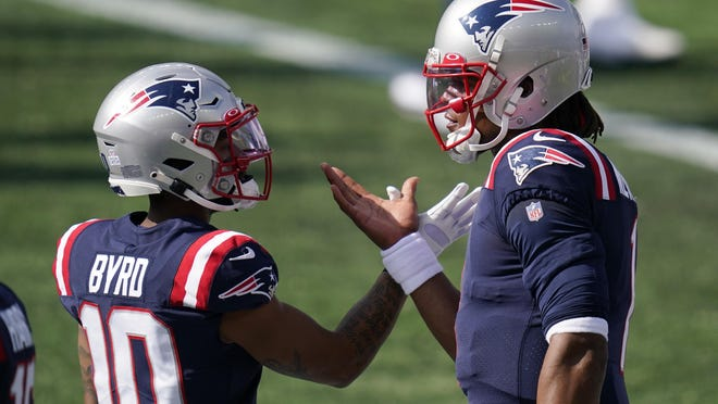 New England Patriots wide receiver Damiere Byrd, left, and quarterback Cam Newton interact as the team warms up before an NFL football game against the Denver Broncos, Sunday, Oct. 18, 2020, in Foxborough, Mass.