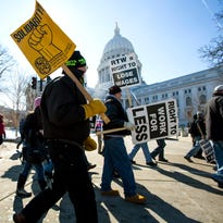 """Protesters march around the state Capitol in Madison after participating in a rally against a """"right-to-work"""" proposal on Saturday."""