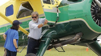 Harrison Ford opens the door on his plane at the Experimental Aircraft Associations AirVenture air show at Wittman Regional Airport in Oshkosh, Wis. in July 2016.