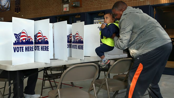 Keith Shelton picks up his son Luca Shelton, 2, after filing out his ballot at the polling station in the Immaculate Heart of Mary school gym in St. Louis on April 5.
