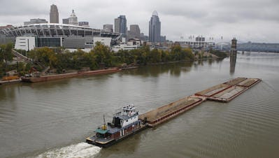 A barge moves cargo on the Ohio River past downtown Cincinnati.