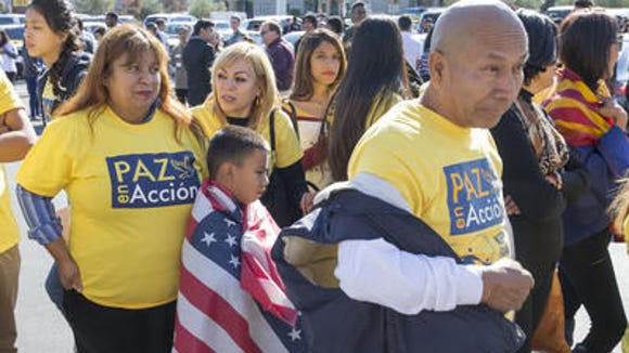 Maria Olague, on left, of Promise Arizona with her son Jonathan Montonada, 7, wears U.S. flag while they wait in line for President Obama's rally at Del Sol High School in Las Vegas on Friday, Nov. 21, 2014.