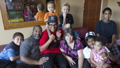 The Williams family poses for a photo at their home in Phoenix in 2011. Nancy Williams has been a licensed foster parent for over 17 years. She and her husband had adopted seven children as of this photo.