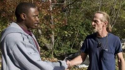 Harold 'Hal' Miller (left), a homeless shelter coordinator accused of running a drug market, greets an unidentified man  at a Camden encampment in December 2010.