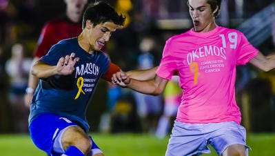 Leutrim Shefkiu, left, of Mason attempts to dribble by Ben Meschke of Okemos during their game, which was also a fundraiser for Compete for a Cause in Okemos. Shefkiu is the LSJ boys soccer player of the year.