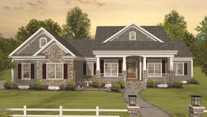 A wide porch with tapered columns and touches of stone add Craftsman flair to this home's exterior.